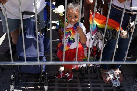 A child watches as participants take part in the LGBT Pride March in the Manhattan borough of New York City, U.S.,  June 25, 2017. REUTERS/Carlo Allegri