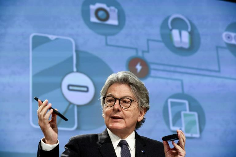 EU internal market commission Thierry Breton shows his phone as Brussels seeks to impose a universal charger (AFP/Kenzo TRIBOUILLARD)