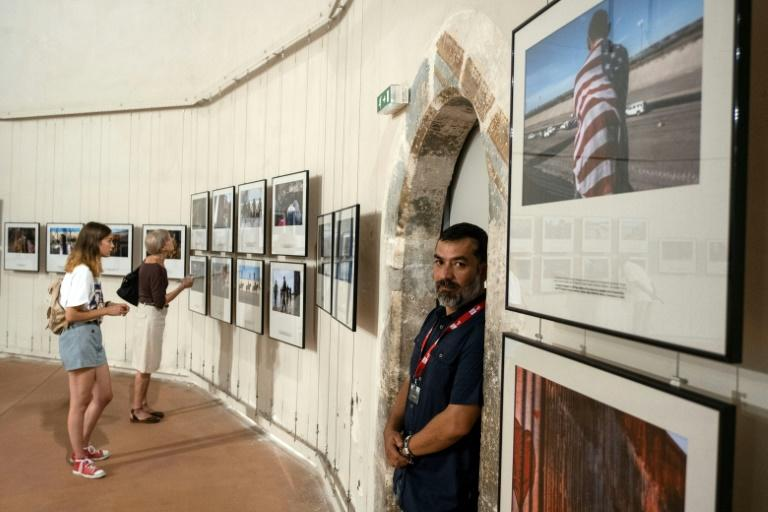 """Mexican photojournalist Guillermo Arias poses at his exhibition """"The Caravan"""" at the Couvent Des Minimes during the Visa Pour l'Image festival in Perpignan, France, on September 3, 2019.Arias won the Visa d'or News award in Perpignan on September 7, 2019"""
