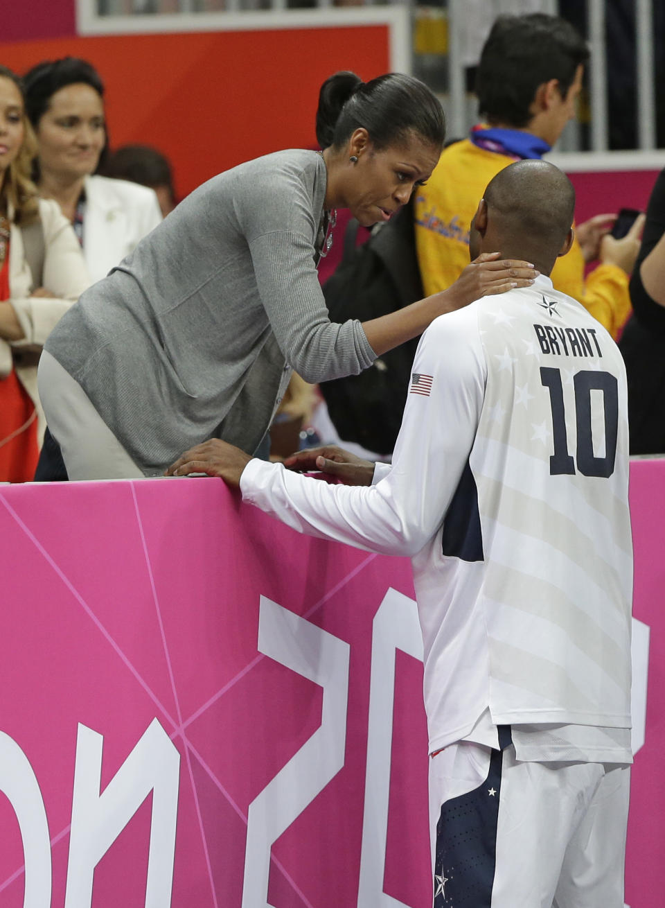 First Lady Michelle Obama talks with USA's Kobe Bryant after USA defeated France in a preliminary men's basketball game at the 2012 Summer Olympics, Sunday, July 29, 2012, in London. (AP Photo/Eric Gay)