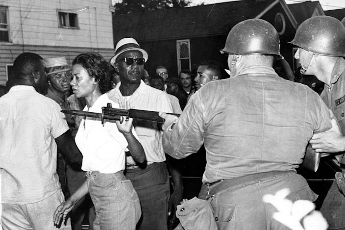 FILE - In this July 21, 1963, file photo, Gloria Richardson, head of the Cambridge Nonviolent Action Committee, pushes a National Guardsman's bayonet aside as she moves among a crowd of African Americans to convince them to disperse in Cambridge, Md. Richardson, an influential yet largely unsung civil rights pioneer whose determination not to back down while protesting racial inequality was captured in a photograph as she pushed away the bayonet of a National Guardsman, died Thursday, July 15, 2021, in New York, according to Joe Orange, her son in law. She was 99. (AP Photo/File)