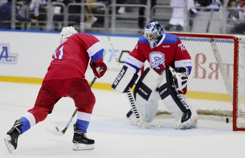 Russian President Vladimir Putin, left, tries to score during an ice hockey game at Bolshoi Arena in the Black sea resort of Sochi, Russia, Friday, May 10, 2019. (Mikhail Klimentyev, Sputnik, Kremlin Pool Photo via AP)