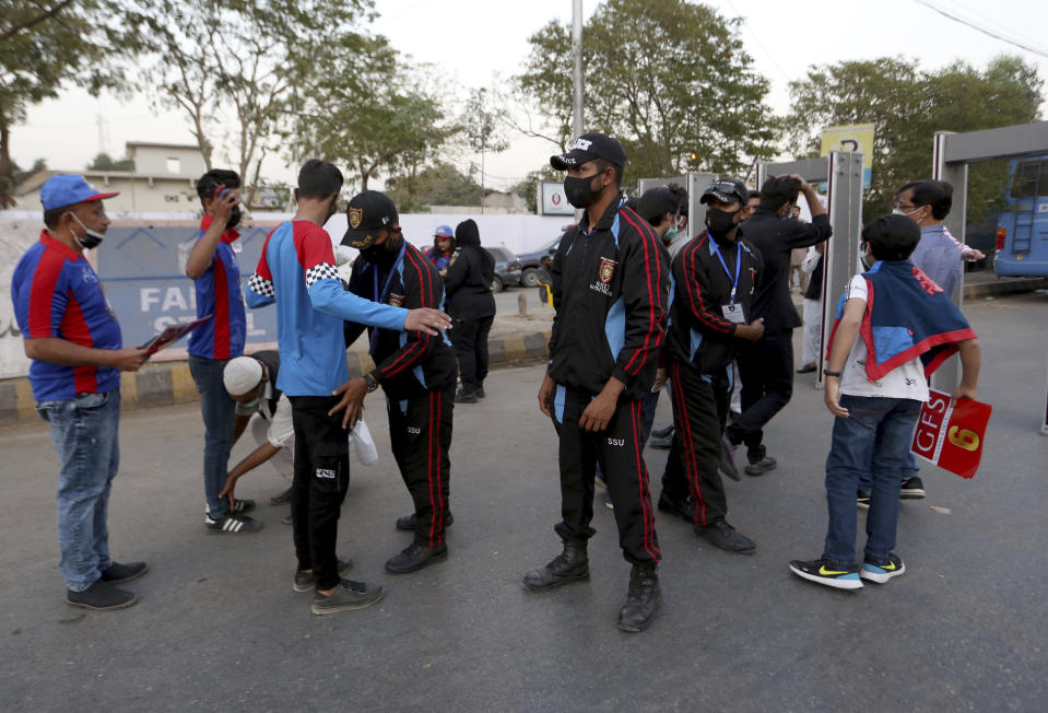 Pakistan police officers frisk cricket fans upon their arrival at the National Stadium to watch Pakistan Super League T20 cricket opening match between Karachi Kings and Quetta Gladiators at National Stadium, in Karachi, Pakistan, Saturday, Feb. 20 2021. Spectators returned to cricket stadiums in Pakistan for the first time since the coronavirus pandemic began when the sixth edition of the Pakistan Super League begins in the southern port city of Karachi. (AP Photo/Fareed Khan)