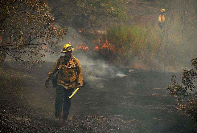 <p>A Los Angeles city firefighter walks through a charred field as he looks for hot spots after the Carr Fire burned through the area on July 29, 2018 in Redding, Calif. (Photo: Justin Sullivan/Getty Images) </p>
