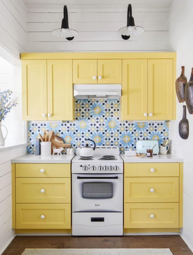 """<p>In order to complement this exciting tile backsplash, these kitchen cabinets needed a fresh coat of paint that shined just as bright. <a href=""""https://www.sherwin-williams.com/homeowners/color/find-and-explore-colors/paint-colors-by-family/SW9018-honey-bees"""" rel=""""nofollow noopener"""" target=""""_blank"""" data-ylk=""""slk:Honey Bees by Sherwin-Williams"""" class=""""link rapid-noclick-resp"""">Honey Bees by Sherwin-Williams</a> did just the trick to finish out the ultimate country color combo of blue, yellow, and white in this 98-square-foot kitchen.</p>"""