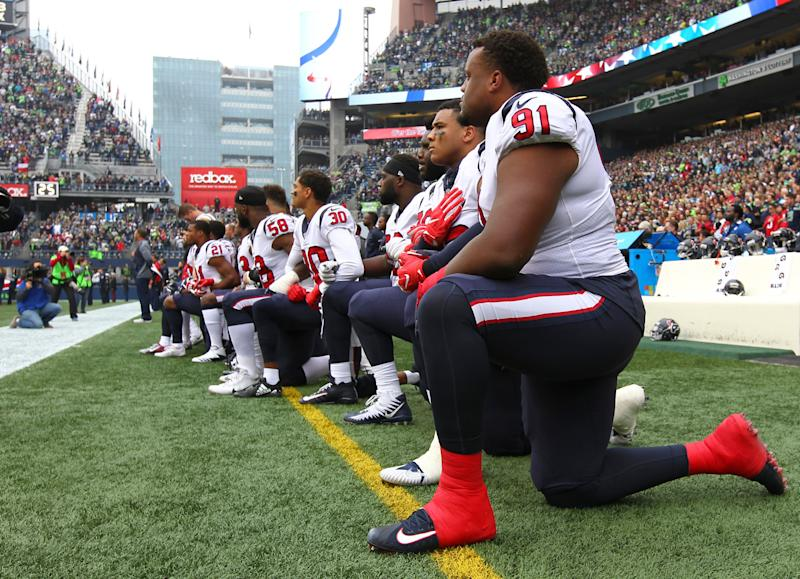Texans player Carlos Watkins is pictured kneeling with his teammates on Sunday.