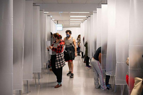 PHOTO: Residents of Cuyahoga county, separated by plastic due to health concerns amid the coronavirus pandemic, arrive to fill out paper ballots for early, in person voting at the board of elections office in downtown Cleveland, Oct. 16, 2020. (Dustin Franz/AFP via Getty Images)