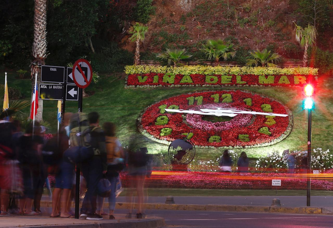 Tourists stand in front of a giant clock made of flowers in Vina del Mar, Chile, January 23, 2018. REUTERS/Rodrigo Garrido