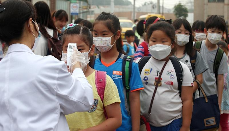 A health worker checks the body heat of children wearing face masks at an elementary school in Pyeongtaek, south of Seoul, on June 15, 2015 (AFP Photo/)