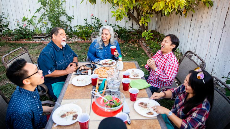 Diverse group of friends having dinner outdoors at a backyard bbq.