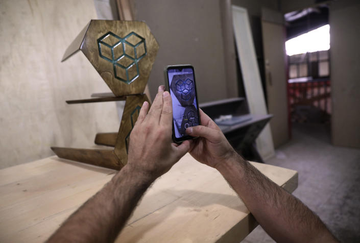 Woodworker Ali Hedieloo takes a photo of his products to post on social media at his furniture workshop in the southern suburbs of Tehran, Iran, Friday, July 30, 2021. New legislation proposed by Iran's hard-line lawmakers that is designed to restrict access to social media applications in Iran has sent a wave of panic through society, stirring concerns among young Iranians, social media users and business owners. Like an estimated 1 million other Iranians, Hedieloo uses social media to find customers. (AP Photo/Vahid Salemi)