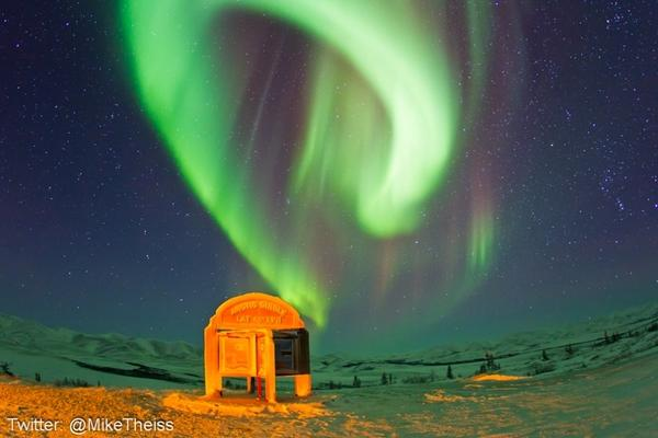 The northern lights above a sign marking the edge of the Arctic Circle.
