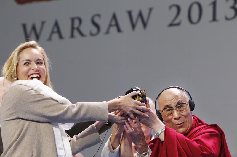 US actress Sharon Stone,left, receives the Nobel Peace laureates summit Peace Prize from the Dalai Lama in Warsaw, Poland, Wednesday, Oct. 23, 2013. Stone was awarded in recognition of her activities against HIV and AIDS. (AP Photo/Czarek Sokolowski)