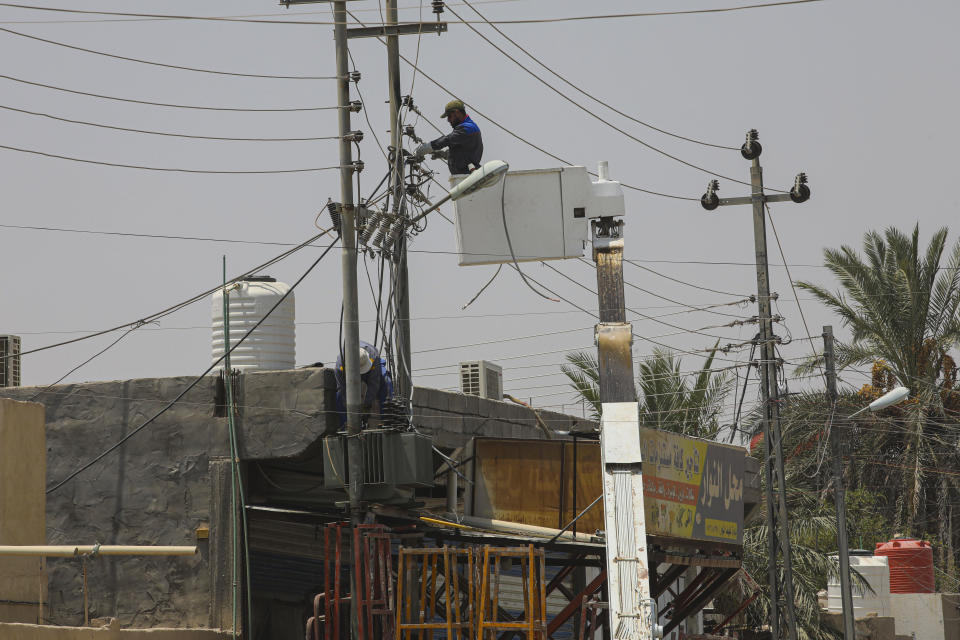 Ministry of Electricity workers are trying to maintain the electricity transmission network in Basra, Iraq, Thursday, July. 30, 2020. As temperatures soar to record levels this summer, Iraq's power supply falls short of demand again, providing a spark for renewed anti-government protests. Amid a nationwide virus lockdown, homes are without electricity for hours in the blistering heat. (AP Photo/Nabil al-Jurani)