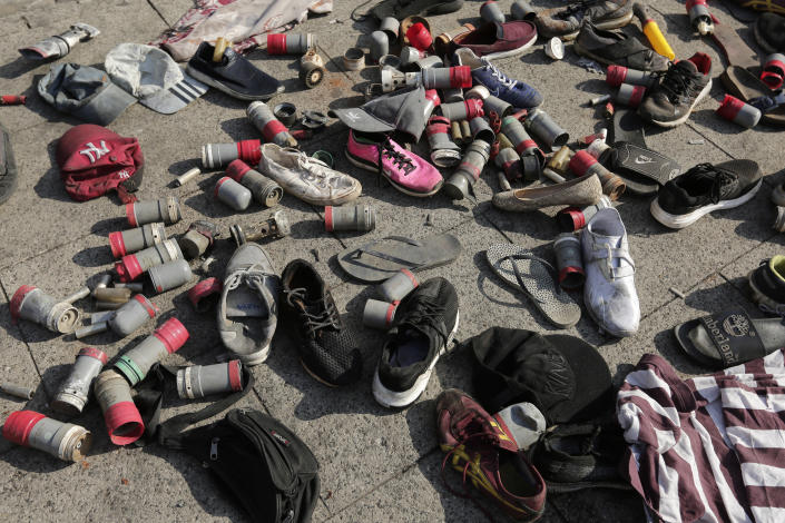 "Tear gas canisters used by the Lebanese riot police and shoes left by protesters collected on the street in the aftermath of a protest against the Lebanese government in Beirut, Lebanon, Saturday, Oct. 19, 2019. The blaze of protests was unleashed a day earlier when the government announced a slate of new proposed taxes, including a $6 monthly fee for using Whatsapp voice calls. Arabic on the wall reads ""Revolution, left, Leave,"". (AP Photo/Hassan Ammar)"