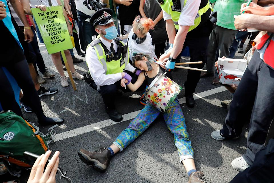 Police officers wearing face masks and gloves due to the COVID-19 pandemic, detain an activist from the climate protest group Extinction Rebellion as they demonstrate in Parliament Square in London on September 2, 2020, on the second day of their latest season of