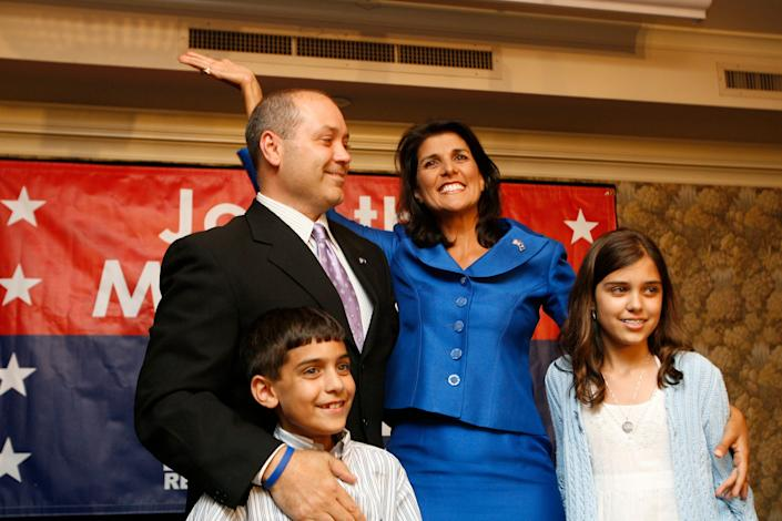 ORG XMIT: SCCOL101 Nikki Haley waves with her family in Columbia, S.C. during an election night gathering on Tuesday, June 8, 2010. Haley brushed aside unproven accusations of extramarital affairs to win a spot in a runoff Tuesday for the GOP nomination for governor, nearly winning the nomination outright in a bid to become the first woman to hold the office. (AP Photo/Rich Glickstein/The State)