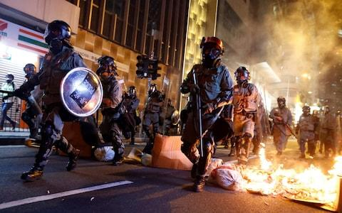 <span>Police passes a burning barricade to break up thousands of anti-government protesters</span> <span>Credit: THOMAS PETER/REUTERS </span>