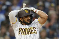 San Diego Padres' Fernando Tatis Jr. adjusts his helmet before striking out during the third inning of the team's baseball game against the Los Angeles Dodgers, Thursday, Aug. 26, 2021, in San Diego. (AP Photo/Gregory Bull)