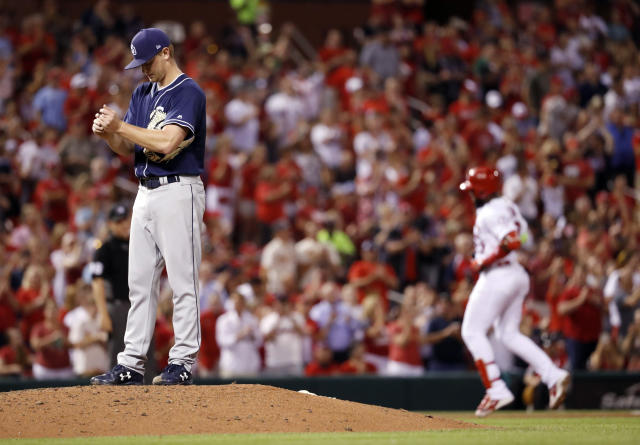 San Diego Padres starting pitcher Eric Lauer, left, rubs up a new ball as St. Louis Cardinals' Marcell Ozuna rounds the bases after hitting a two-run home run during the sixth inning of a baseball game Wednesday, June 13, 2018, in St. Louis. (AP Photo/Jeff Roberson)