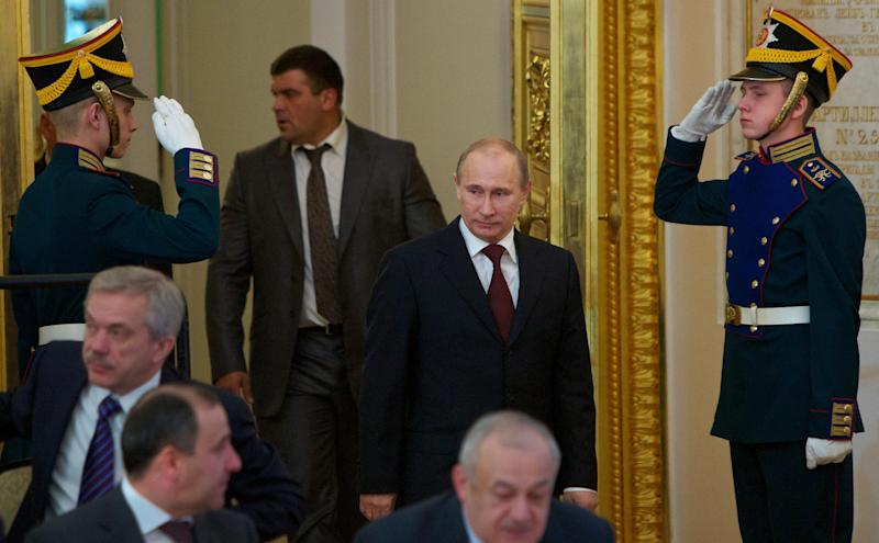 Russian Prime Minister Vladimir Putin, center, enters the The St. George hall to hear Russian President Dmitry Medvedev's addressing the State Council in the Kremlin in Moscow, Russia, Tuesday, April 24, 2012. Medvedev, who will shift into the prime minister's job after Vladimir Putin reclaims the presidency next month, summed up the results of his four-year presidency and set goals for the future.(AP Photo/Alexander Zemlianichenko)
