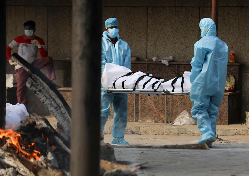 Health workers wearing Personal Protective Equipment (PPE) carry the body of a covid19 victim during the mass cremation at Dwarka crematorium.