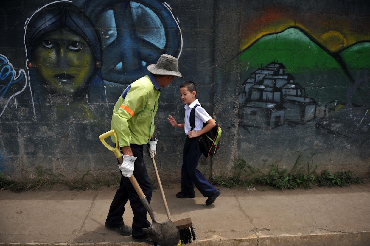 Costa Rican child Gerald Sequeira, 8, greets a sweeper while going to school on Aug. 22, 2013.