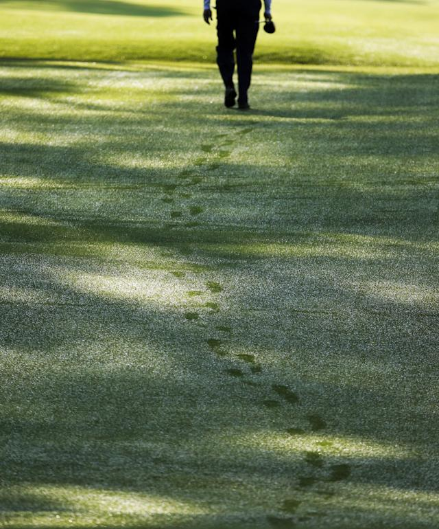 D.A. Points walks through wet grass after teeing off on the seventh hole during the second round of the Masters golf tournament Friday, April 11, 2014, in Augusta, Ga. (AP Photo/Charlie Riedel)
