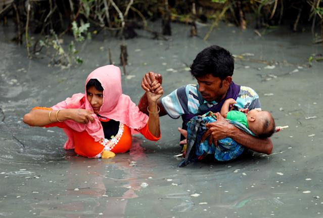 <p>Rohingya refugees carry their child as they walk through water after crossing border by boat through the Naf River in Teknaf, Bangladesh, Sept. 7, 2017. (Photo: Mohammad Ponir Hossain/Reuters) </p>