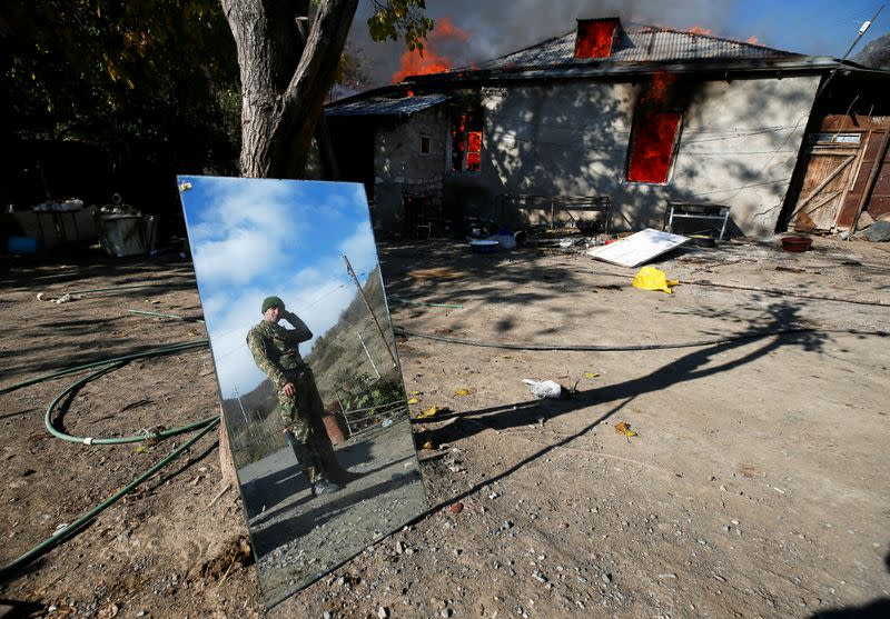 A man is reflected in a mirror as he stands near a house set on fire by departing Ethnic Armenians in the village of Cherektar, in the region of Nagorno-Karabakh