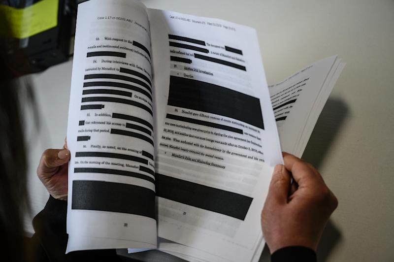 A journalist reads a redacted court filing from Special Council Robert Mueller; many worry that key parts of his final report will be similarly censored (AFP Photo/Eric BARADAT)