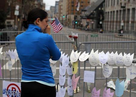 Allison Petrone cries while paying her respects to the victims of the Boston Marathon bombings at a memorial at the barricade surrounding the scene of the explosions in Boston
