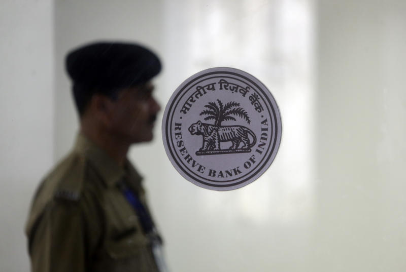 An Indian security guard stands at the gate of the Reserve Bank of India in Mumbai, India, Thursday, June 6, 2019. India's central bank has cut its key interest rate by a quarter of a percentage point to 5.75% from 6% with immediate effect to fortify the economy as consumer spending and corporate investment falter. (AP Photo/Rajanish Kakade)
