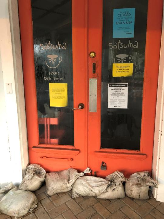 Sandbags are in place at Satsuma restaurant in New Orleans on Saturday, Aug. 28, 2021. Normally bustling on a weekend morning, the popular breakfast spot was closed while taking protections against possible flash floods as Hurricane Ida approached the Louisiana coast. (AP Photo/Kevin McGill)