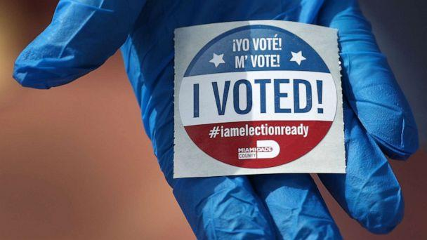 PHOTO: A voter holds an, 'I Voted!', sticker after wearing a glove as she cast her ballot during the Florida presidential primary as the coronavirus pandemic continues on March 17, 2020, in Miami Beach, Fla. (Joe Raedle/Getty Images)