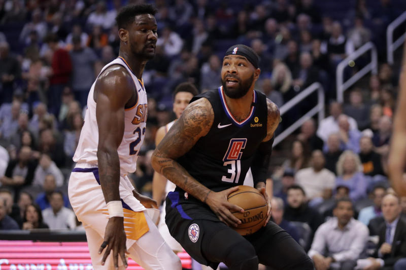 Los Angeles Clippers forward Marcus Morris Sr. (31) looks to shoot over Phoenix Suns center Deandre Ayton (22) during the first half of an NBA basketball game, Wednesday, Feb. 26, 2020, in Phoenix. (AP Photo/Matt York)