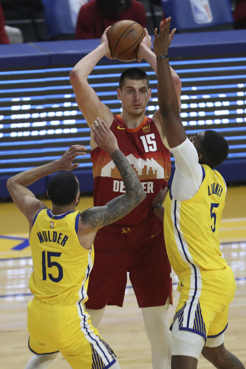 Golden State Warriors' Mychal Mulder, left, and Kevon Looney defend against Denver Nuggets' Nikola Jokic during the first half of an NBA basketball game in San Francisco, Friday, April 23, 2021. (AP Photo/Jed Jacobsohn)