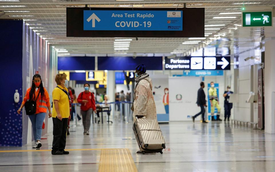 People are seen along an airport corridor, after Italy made testing compulsory for travellers from parts of France that have a high number of cases, at the Fiumicino Airport in Rome - Remo Casilli/Reuters