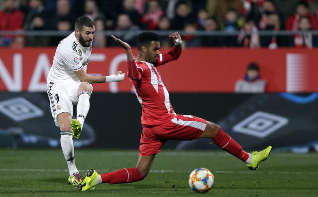 Real Madrid's Benzema, left, duels for the ball with Girona's Jonas Ramalho during a Spanish Copa del Rey soccer match between Girona and Real Madrid at the Montilivi stadium in Girona, Spain, Thursday, Jan. 31, 2019. (AP Photo/Manu Fernandez)