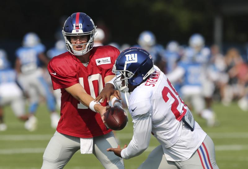 New York Giants quarterback Eli Manning hands off to running back Jonathan Stewart during a joint practice at the Detroit Lions football training facility, Tuesday, Aug. 14, 2018, in Allen Park, Mich. (AP Photo/Carlos Osorio)