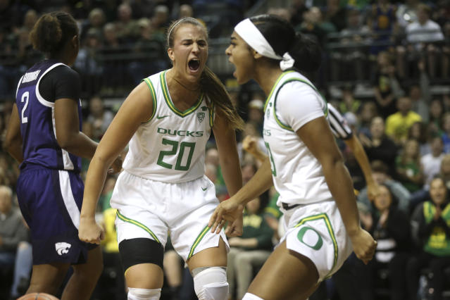 Oregon's Sabrina Ionescu, center, and Minyon Moore celebrate a play in the second quarter of an NCAA college basketball game against Kansas State in Eugene, Ore., Saturday, Dec. 21, 2019. (AP Photo/Chris Pietsch)