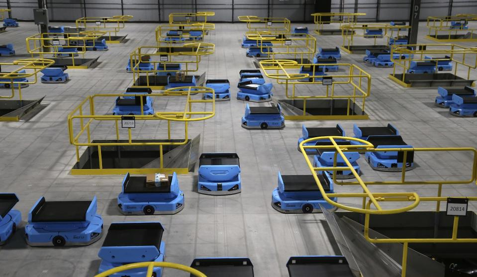 In this Dec. 17, 2019, photo dozens of Amazon robots transport packages from workers to chutes that are organized by zip code, at an Amazon warehouse facility in Goodyear, Ariz. Amazon and its rivals are increasingly requiring warehouse employees to get used to working with robots. (AP Photo/Ross D. Franklin)