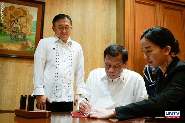"Senator Christopher Lawrence ""Bong"" Go (left) looks on as President Rodrigo Duterte (center) signs the Salary Standardization Law of 2019."