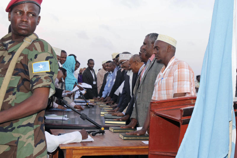 New Somali members of parliament put their hands on the Quran to take an oath during the swearing in ceremony of 211 MP's at Aden Ade international airport in Mogadishu, Somalia, Monday, Aug 20, 2012. Somalia's newly-selected members of parliament were on Monday sworn in as the Horn of Africa country moves from the long-drawn transitional period to a permanent form of government. (AP Photo/Farah Abdi Warsamehmeh)