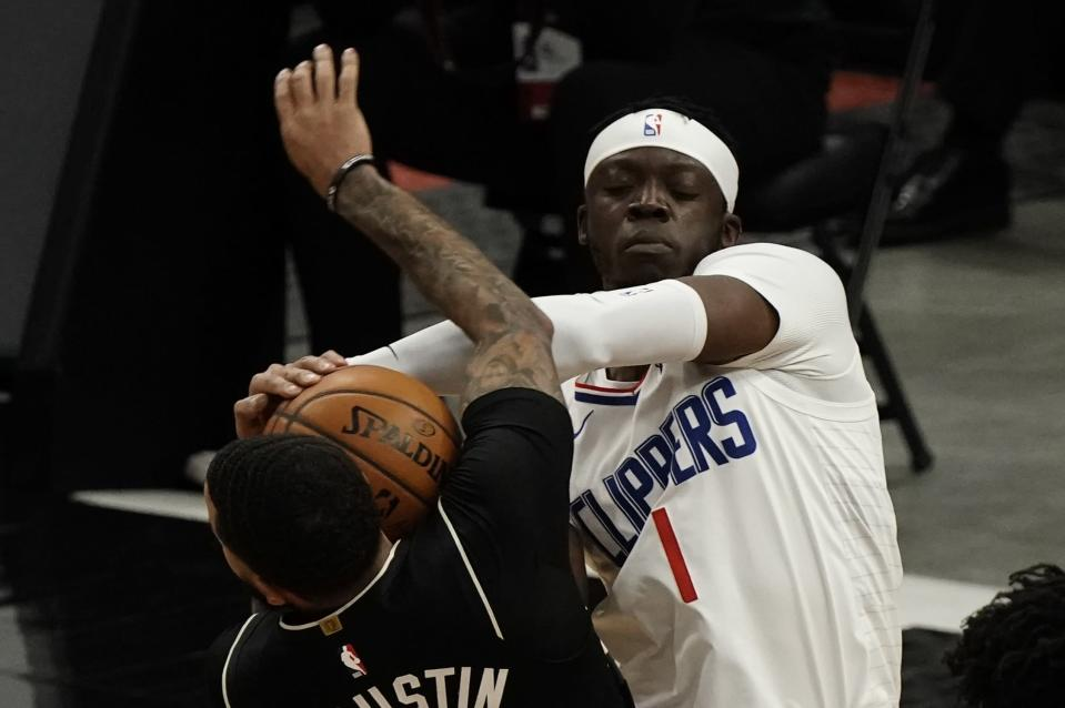 LA Clippers' Reggie Jackson ties up Milwaukee Bucks' D.J. Augustin during the first half of an NBA basketball game Sunday, Feb. 28, 2021, in Milwaukee. (AP Photo/Morry Gash)