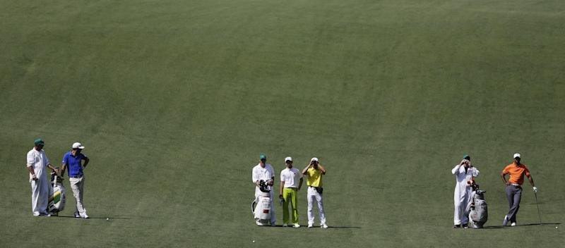 From left, Dustin Johnson, Amateur Guan Tianlang, of China, and Tiger Woods along with their caddies wait to play on the 10th fairway during a practice round for the Masters golf tournament Monday, April 8, 2013, in Augusta, Ga. (AP Photo/David Goldman)