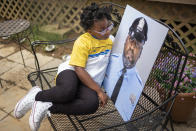 """Amethyst, the five-year old daughter of Erin """"Toke"""" Tokley, a Philadelphia cop who died from COVID-19 in March, poses with a portrait of her father on Aug. 29, 2021, in Secane, Pa. Tokley was scheduled to be vaccinated on March 11 – which turned out to be his funeral. (AP Photo/Laurence Kesterson)"""
