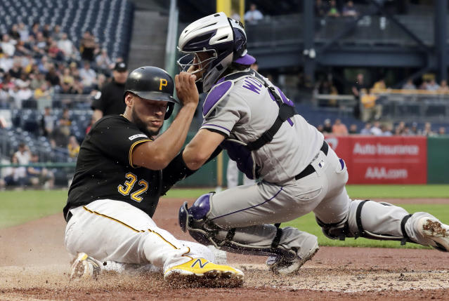 Pittsburgh Pirates' Elias Diaz (32) scores ahead of the tag attempted by Colorado Rockies catcher Tony Wolters during the second inning of a baseball game in Pittsburgh, Wednesday, May 22, 2019. (AP Photo/Gene J. Puskar)