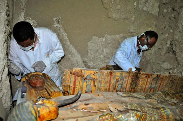 Members of an Egyptian archaeological team work on April 18, 2017 on a wooden coffin discovered in a 3,500-year-old tomb in the Draa Abul Nagaa necropolis, near the southern Egyptian city of Luxor (AFP Photo/STRINGER)