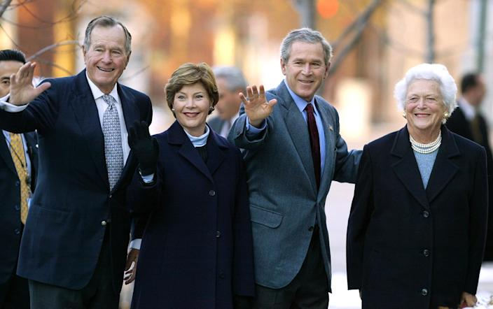 <p>Former President George H.W. Bush (left), first lady Laura Bush, President George W. Bush and former first lady Barbara Bush wave to reporters outside St. John's Church in Washington, D.C., on Dec. 7, 2003. (Photo: Evan Vucci/AP) </p>